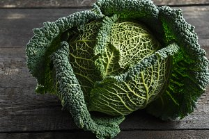 Savoy cabbage on a background of a dark wooden table