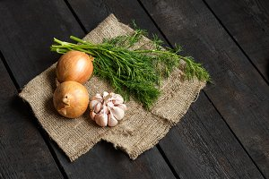 Ingredients for soup or salad: onion, garlic, dill on a dark background