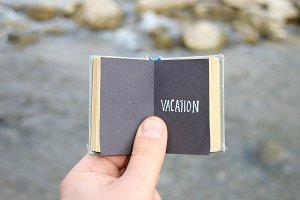 vacation concept, traveler holds a book with text