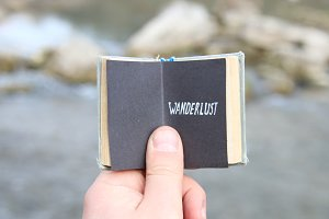 Wanderlust concept, The traveler holds a book with text