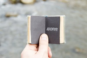 Adventure. The traveler holds a book with text