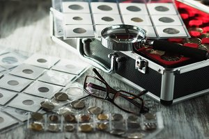 Different old coins, glasses and magnifying glass, Soft focus background