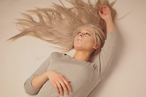 Blonde model girl lying in photo studio - close up view