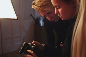 Blonde girl model and photographer in photo studio watching photos in camera, fashion backstage