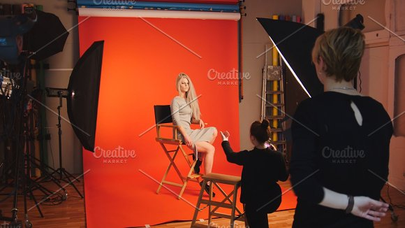 Blonde model girl lying in photo studio - photographer and make up artist straightens hair, fashion backstage