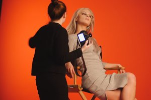 Blonde model girl in photo studio - photographer straightens hair, fashion backstage