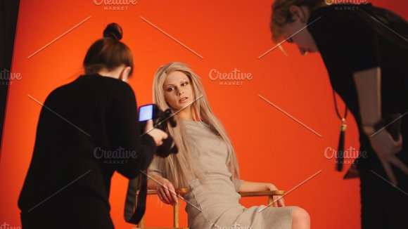 Blonde model girl lying in photo studio - photographer and make up artist straightens hair, fashion backstage in Graphics