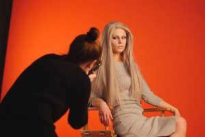 Backstage: blonde female model posing for photographer in red studio