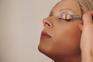 Makeup artist makes handsome models eye makeup by brush