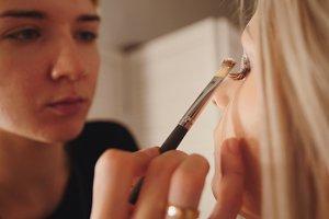Makeup artist makes handsome models eye makeup