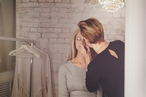 Beauty salon - makeup artist and blonde model near mirror in the dressing room