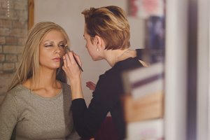 Visage - makeup artist and blonde model near mirror in the dressing room