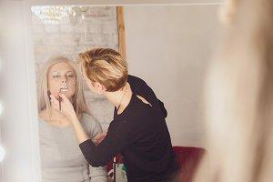Beauty shop: makeup artist creates makeup attractive young woman near evening window