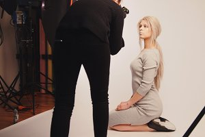 Workshop backstage - Blonde handsome girl posing for photographer - model sits at knees