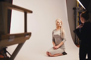 Fashion photo backstage - Blonde handsome girl posing for photographer - model sits at knees