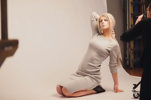 Fashion photo backstage - attractive model posing for photographer - girl sits at knees