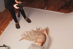 Attractive blonde model girl lying in photo studio - posing for photographer