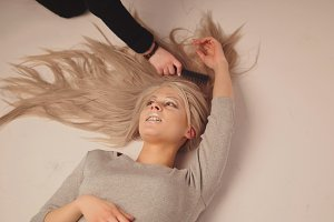 Blonde model girl lying in photo studio - photographer combing the hair of the model, top view