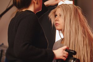 Blonde white caucasian model girl in photo studio - photographer straightens hair, fashion backstage