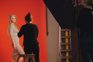 Photo backstage: blonde girl model plays long hair - photographer take a picture in studio