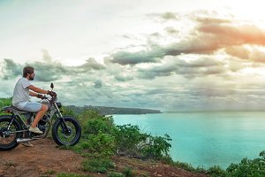 Biker sitting on vintage custom motorcycle. Outdoor lifestyle portrait