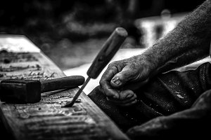 Black and white photo of men's hands that putting a paint on a little piece of wooden detail wallpaper. Old and vintage hobby background. Industrial art of wooden work surface