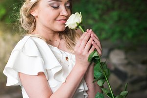 beautiful girl sniffing white rose
