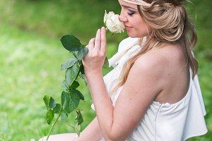 beautiful girl sniffing white rose