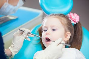 Little girl sitts in the dentist's office