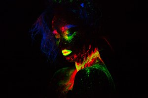 Beautiful extraterrestrial model woman with blue heair and green lips in neon light. It is portrait of beautiful model with fluorescent make-up, Art design of female posing in UV with colorful make up. Isolated on black background