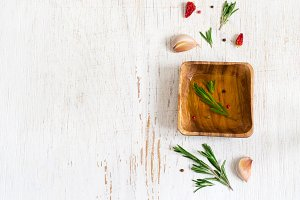 Olive oil with rosemary in a wooden bowl and spices. Top view wi