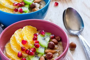 Healthy breakfast oatmeal with different fruits, pomegranate and
