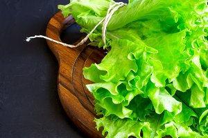 Lettuce on a wooden cutting board on a dark background, copy spa