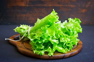 Lettuce on a wooden cutting board on a dark background