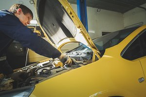 A worker mechanic checks the electrical in the hood of the yellow car, garage workshop