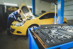 Defocused - a worker mechanic checks the electrical in the hood of the yellow car, garage workshop