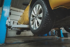 Car service - lifted yellow automobile in garage workshop