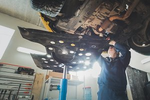 Car automobile service - mechanic checks the bottom of car