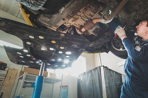 Car automobile service - worker mechanic checks the bottom of car