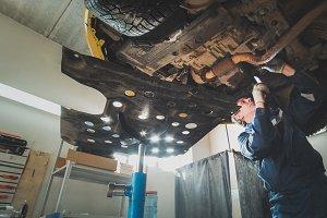 Worker mechanic checks the bottom of car - automobile service