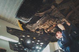 Under bottom of car - Worker mechanic checks - automobile service