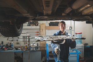 Male caucasian worker - mechanic in automobile garage repairing workshop - under lifted car