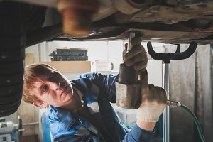 Mechanic with screwdriver in automobile garage - Man caucasian worker - repairing workshop - under lifted car