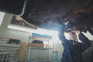 Mechanical auto workshop - a mechanic checks the suspension of car, wide angle