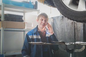 Garage automobile service - a mechanic near lifted car speaks on cellphone