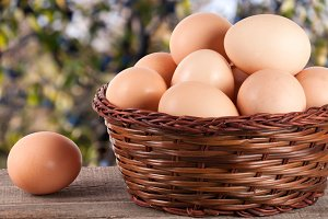 eggs on a wooden table in a wicker basket with blurred garden background