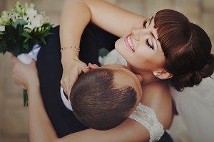 Groom kisses bride's shining skin