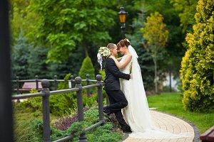 Bride in long veil hugs a groom