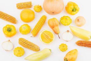 Background from yellow and orange fresh raw vegetables and fruits, light background