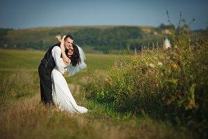 Bride twindes her hands around groom